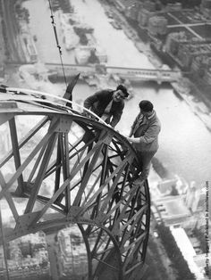 electricians work on lights of the Eiffel Tower which will illuminate the Paris Exhibition 1937.