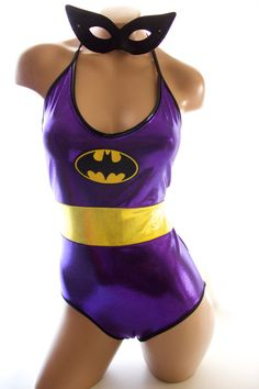 Sugarpuss Old School Batgirl Custom Costume One-Piece Bodysuit in Purple Metallic Lycra with Batman Patch  This unique and sexy Batgirl inspired bodysuit gets its inspiration from the original Batgirl, Yvonne Craig. The suit takes the best of our Sugarpuss bodysuits and one-pieces and combines it with our sexy Batman costume details to give you a one of a kind suit!  The top half has a deep V in royal purple metallic lycra in front trimmed in the black shiny lycra with a halter tie around…