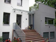 Modern gestaltetes Vordach aus Stahl und Glas