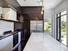 Carrara marble counters, subway tile backsplash, stainless steel appliances, and walls of sleek cabinetry in white and espresso