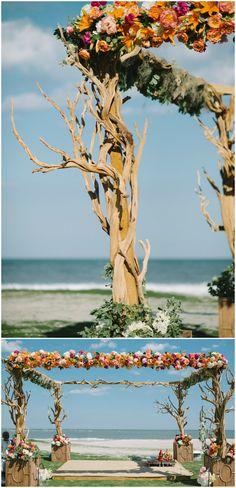 Beach wedding ceremony, large arbor, twisting branches, colorful florals, seaside nuptials // Sean Money + Elizabeth Fay
