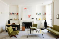 Modern, Parisian living space with green furniture and open shelving