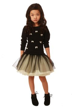 Fall 2015: Ooh! La, La! Couture, at the Curly Girls Showroom, blends school girl charm with a ballerina's beauty and grace. The Plaid Schoolgirl works grunge with a full mini tutu. Classic black and white looks fresh strewn with bows and buoyant with tulle. www.curlygirlsshowroom.com, www.oohlalacouture.com (designer preview)