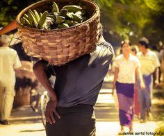 Mann mit schwerem Korb voller Bananen