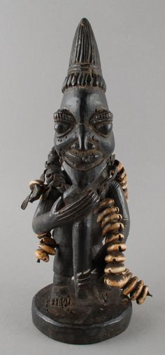 Yoruba Ogo Elegba (staff of Eshu, Orisha of uncertainty, change and sexual energy). Depicts Eshu or an Eshu priest playing the flute. Elongated phallic coiffure, symbolic of Eshu's spiritual power and sexual energy. Cowrie shells are symbolic of Fortune. Africa Art, West Africa, Voodoo, African Sculptures, Yoruba, Art Africain, Floral Photography, African Masks, Religious Art