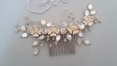 This hair comb is completely wired by hand with: -Vintage style raw brass plating silver flowers (silver colors with light Ivory shadow) -Mother of Pearl Shell Carved Leaves (Ivory) -Toho seed beads (silver colors with light Ivory shadow) -Swarovski crystals (Moon Light Shadows) Width
