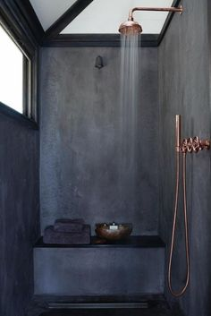 A beautiful dark bathroom finished with stunning copper shower and copper fixtures. Wow!