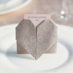 The ancient art of Japanese paper folding was used to make this romantic design, complete with a pocket for a place card. Choose 6-inch square origami papers with a pretty pattern or different color on each side; both will be visible in the heart.