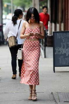 Vanessa Hudgens:conjunto de cropped top y falda entubada de color salmón con lunares blancos de Reformation, sandalias con tachuelas, bolso blanco con detalles metálicos de Om y gafas de sol.