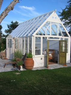 Beautiful;y designed greenhouse with vintage doors, brick floors, and stone for the out side. Isas Trädgård: Växthusbygge