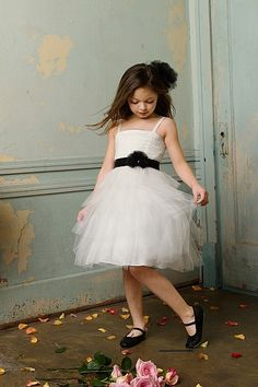Beautiful dress with tulle and shirred bodice. Tiered knee skirt with a black satin and grosgrain flower belt.