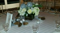 Glass cube arranged with hydrangea and Pola roses, lisianthus, silver balls, winter pine and pine cones surrounded by pine cones and snow.