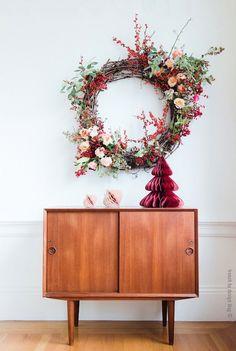 Optez pour une couronne de Noel originale, remplie de fleurs et de baies rouges