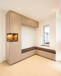 Dieses Flurmöbel mit lederbezogener Sitzbank über Eck bildet die Garderobe des Hauses.  Der Schrank ist braun matt beschichtet, verfügt über Schubladen für Schuhe und eine Kleiderstange aus Edelstahl.  Eine Nische in Räuchereiche Echtholz mit indirekter Beleuchtung bietet Platz für z.B. Schlüssel oder Handys.