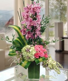 A Dazzling fresh flower arrangement of cymbidium orchids, pink roses,full-bloom hydrangea and exotic leaves. A perfect surprise celebration to be enjoyed and remembered!