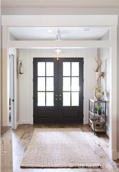 Double front door with paneled windows and gorgeous hardwood
