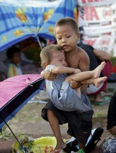 This scene was taken during food distribution at Tacloban Evac Center. These two were not related, the young boy said this:  Hindi ko po siya kapatid. Baka po siya mawala o masaktan kasi madaming tao sa linya. Kukuha nalang po ako ng para sa kanya. TRANSLATION: She is not my sister, I was worried that due to the long lines to get food, she might get lost and get hurt. I will get food for her. www.paulmirador.com