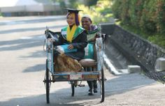 """Very Inspiring: the poor father who was proud with her daughter who achieve GPA 3.96 at the university, he escorting her daughter using his """"becak"""" to the graduation celebration."""