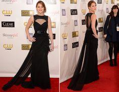 Jennifer Lawrence usou o longo preto da grife Prabal Gurung com cintura bem marcada e decote e a transparência nas costas, moderna e sexy!