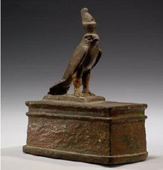 EGYPTIAN BRONZE HORUS FALCON wearing the double crown and standing upon a miniature sarcophagus. XXVIth Dynasty, 664-525 BC.