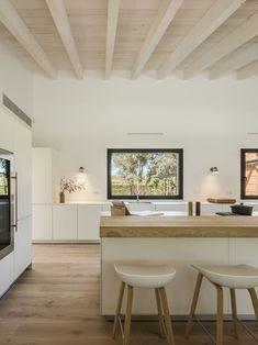Bois Clair du plan de travail et parquet créent une ambiance chaleureuse, et se coordonnent harmonieusement avec les poutres du plafond