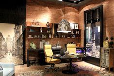 O espaço de 30 m² projetado pelas designers Eliane Cardoso e Fernanda Gonçalves utiliza materiais como couro e o tijolo aparente que conferem aconchego e conforto ao ambiente junto com o piso vinílico rústico Ambienta, cor Jequitibá, fornecido e instalado pela equipe do Ateliê Revestimentos. Os rodapés e guarnições Santa Luzia nas cores preta, também instalados pelo Ateliê, complementam o estilo contemporâneo do home office, junto com o revestimento Decopainel Ripas, também na cor preta.