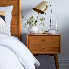 Inspired by mid-century design, our Mid-Century Nightstand borrows its slim legs, angled face and understated retro details from iconic and furniture silhouettes. Choose our standard or charging version, which features two USB sockets an… West Elm Mid Century, Mid Century Bed, Mid Century Console, Mid Century Style, Mid Century Design, 60s Furniture, Bedroom Furniture, Furniture Design, Apartment Furniture