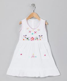 Handmade in the valleys of Ecuador, this breezy frock features handy pockets, back tagua nut buttons and a ruffle hem. Every flower is hand-stitched with variegated thread, making each blossom one of a kind.
