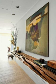 Combine styles for a unique look. A white wall is enhanced with a rustic custom wooden shelf and a large abstract in earthy hues.