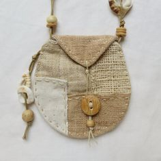 A beautiful patchwork talisman pouch, made using hand woven hemp, indian cotton and natural linen. It has hand stitched details around the edge and the button and beads are made from morlite stone, shell fragments, bamboo and wood. A small flap holds everything in place. These talisman pouches are normally worn around the neck to carry small precious keepsakes. Slowly and carefully handcrafted using all natural materials :) Approximate size of this pouch is 90mm high, by 90mm wide.  Ref…