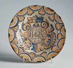 """Talavera, S. XVI. Plato en cerámica esmaltada de la serie """"tricolor"""" con el emblema jesuítico bajo corona, alero con trabajo simulado de encaje de bolillos."""