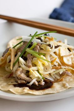 This is not your corner takeout's moo shu pork, but it is wildly popular in China, where its northern origins are debated, according to the author Carolyn Phillips. The egg is thought to resemble the flowers of the sweet olive (osmanthus fragrans) shrub, hence its Chinese name, muxi rou, or osmathus blossom pork. The ingredients are stir-fried in batches to cook evenly and retain the vibrancy of the colors. (Photo: Lisa Nicklin for NYT)