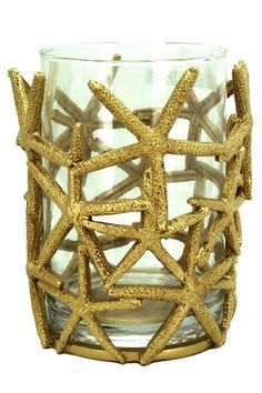 Gold, sculptural starfish wrapped around a glass candle hurricane make this piece a wonderful addition to your beach house; for a coastal themed dining table, foyer table or simply to add an extra festive feeling.