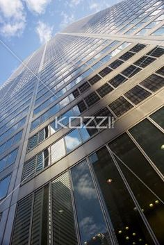 reflection on tall commercial building against sky. - Low angle shot of reflection on office building windows against sky.