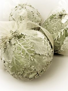 Could be easy to make and how pretty on a white and silver table setting. Mobtown Florals.....no details on these pomanders, but they're silvery plants like Dusty Miller and sage pinned to Styrofoam balls, beautiful.