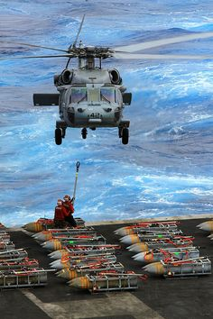 An MH-60S Sea Hawk helicopter assigned to the Dragon Whales of Helicopter Sea Combat Squadron (HSC) 28 picks up ammunition from the aircraft carrier USS Enterprise (CVN 65) during the carrier's last ammunition offload.
