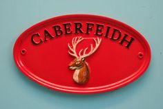 """Oval 12"""" x 7"""" house sign in red with black letters.    Sent to Wales.  www.rockartisansigns.co.uk"""