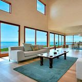Oversized and floor-to-ceiling windows bring in  views  of the Pacific Ocean in this Carmel, Calif., beach house's living room. The living area has ample room for entertaining or just relaxing and enjoying the scenery.  | HGTV FrontDoor