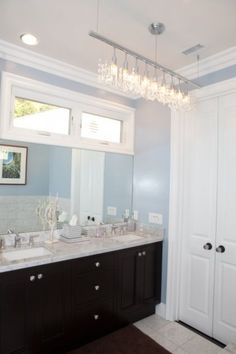 If your bathroom is outfitted with a wide vanity and mirror, pull that sense of width into your bathroom's space with a fixture that involves a bar or track.