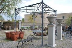 Antique cast iron gazebos make a statement in any garden, as do pergolas built of reclaimed lumber. Here is an acid washed steel pergola with graceful scrolled brackets and orb finials from Detroit Garden Works