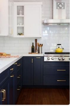 We love the new brass trend! The brass hardware on these black cabinets adds some elegance to this modern kitchen!