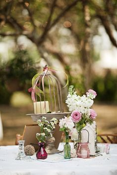 Centerpiece with mixed glass jars, photo frame, cake stand, bird cage, and other odds and ends.