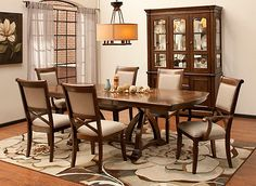 """A caramel finish and sage upholstery make this Jessica 7-piece dining set a perfect fit for your refined dining room. The beautifully patterned tabletop and x-style chair backs offer up an elegant look that's simple yet classic. And if you love to entertain, you'll appreciate this set's thoughtful details, like a 24"""" leaf that provides plenty of extra seating space when you need it and soft, stain-resistant polyester fabric."""