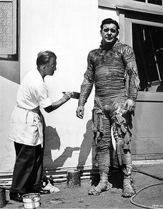 Lon Chaney JR having his Mummy make up touched up by Jack Pierce outside sound stage. (1943)