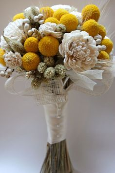 Milk and Honey Bridal Bouquet  Cheery craspedia are combined with sola wood roses and accented with leaves, grasses and berries. The bouquet is collared by a wide mesh raffia ribbon and finished with an ivory satin wrap