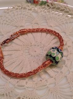 Copper viking knit bracelet with handcrafted ivory, green and blue glass bead by Blueberry Bay Beads