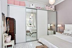 biała szafa z przesuwnymi lustrzanymi drzwiami i różowe pudełka w aranżacji skandynawskiej sypialni