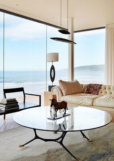 Oceanview living room with a glass coffee table, light walls, large glass windows, cream couch with a patterned blanket, white and black lamp, and a black chair with books