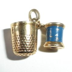 A sweet vintage two piece 14k yellow gold charm for the seamstress or quilter in your life! miniature thimble and spool of thread..
