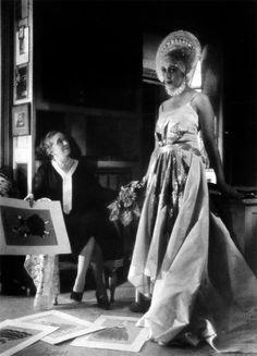 Jeanne Lanvin observes her creation at her Paris studio, 1921.